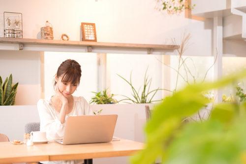 リビングでノートパソコンを見ている女性